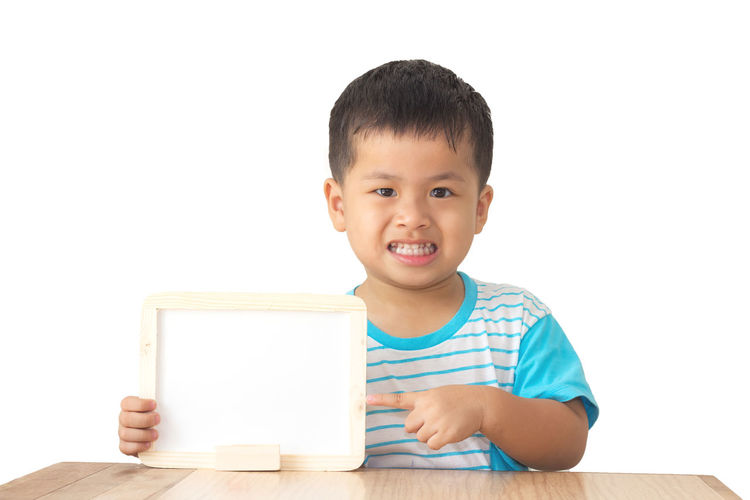 Portrait of cute boy showing whiteboard at table against wall