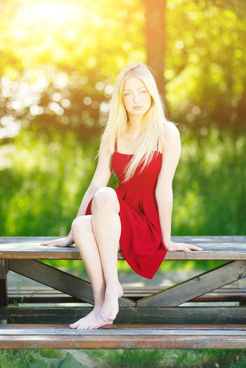 Full length of beautiful young woman sitting on picnic table at park