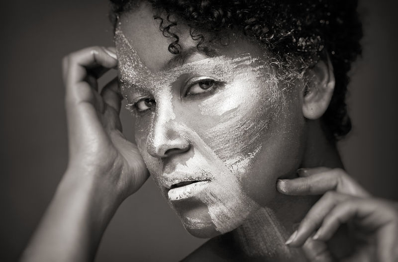 Close-Up Portrait Of Woman With Face Paint Against Gray Background