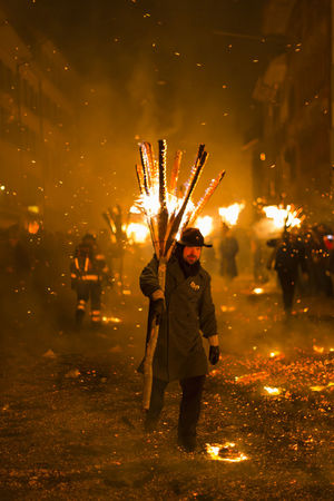 Chienbaese festival. Switzerland, Liestal, Rathausstrasse 25, 18th of February 2018. Festival participants carrying burning broom shaped wooden logs on their shoulders through the old town. Burning Event Flame Hot Old Town Tradition Wood Arts Culture And Entertainment Broom Burning Culture Danger Editorial  Event Festival Fire Heat - Temperature Liestal Motion Night Parade Real People Swiss Switzerland Wood - Material