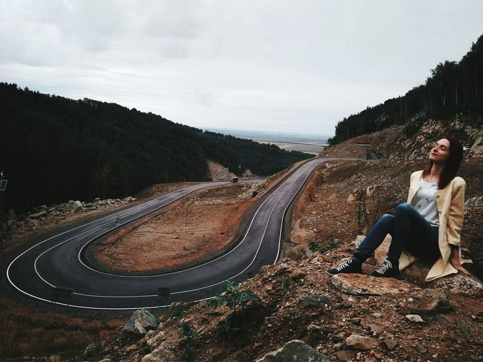 Full Length Of Young Woman Relaxing On Rock By Road At Altai Mountains