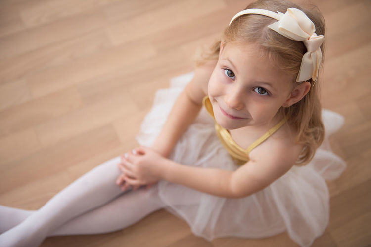 Portrait of ballet dancer sitting on wooden floor