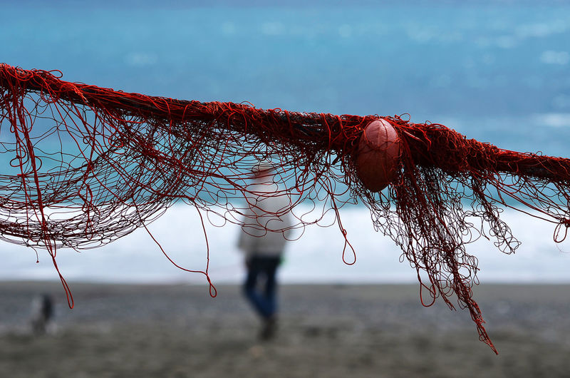 close up of red wires and float for fishing net in front of seaside Beach Beach Life Beach Photography Close-up Floats For Fishing Nets Focus On Foreground On The Beach Outdoors Red Red Wires Seaside Selective Focus Selective Focusing Focus Objects Winter Beach Wires Of Fishing Nets