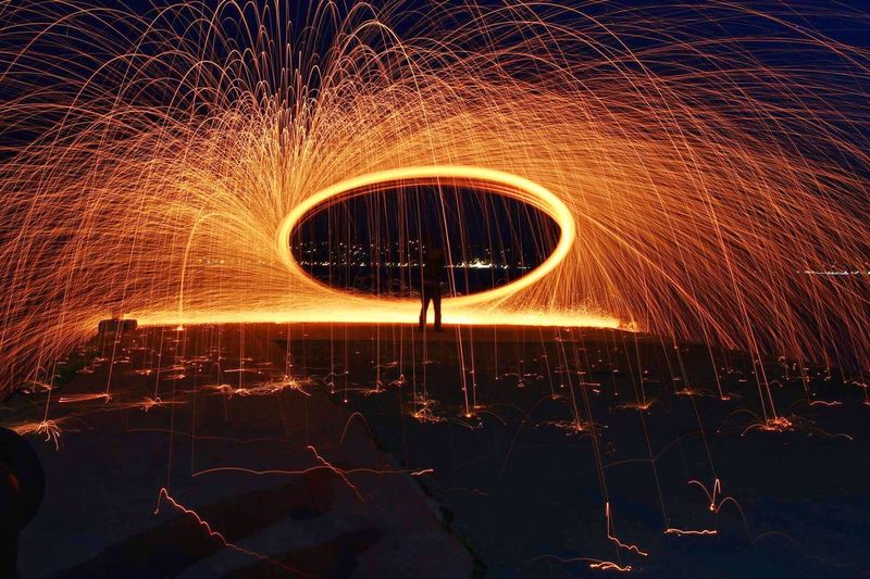Person With Illuminated Wire Wool Standing At Night