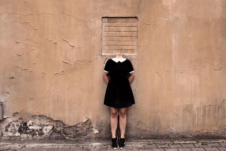 Digital Composite Image Of Decapitated Woman Standing Against Wall