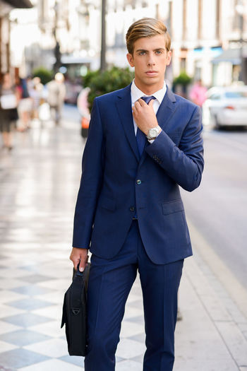Portrait Of Young Businessman Standing On Sidewalk In City
