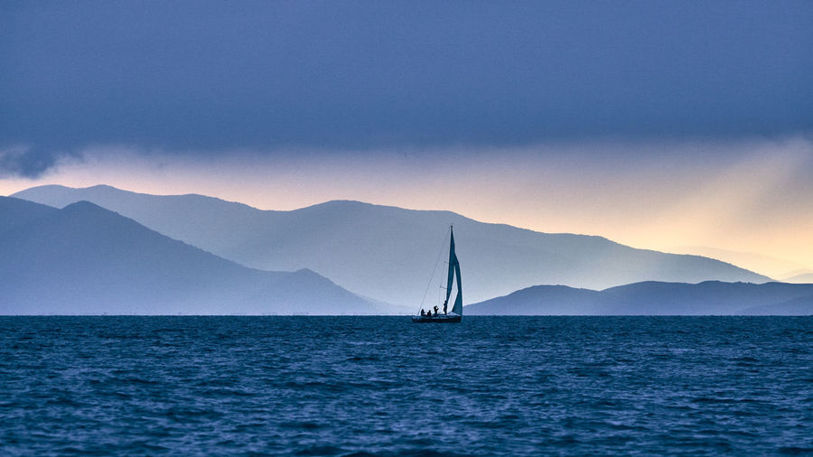 Sailboat sailing on sea against mountains during sunset