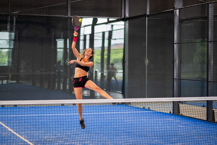 Woman playing padel in a blue grass padel court - young sporty woman padel player hitting ball