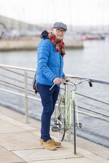Portrait Of Senior Man With Bicycle Walking By Railing Against Sky