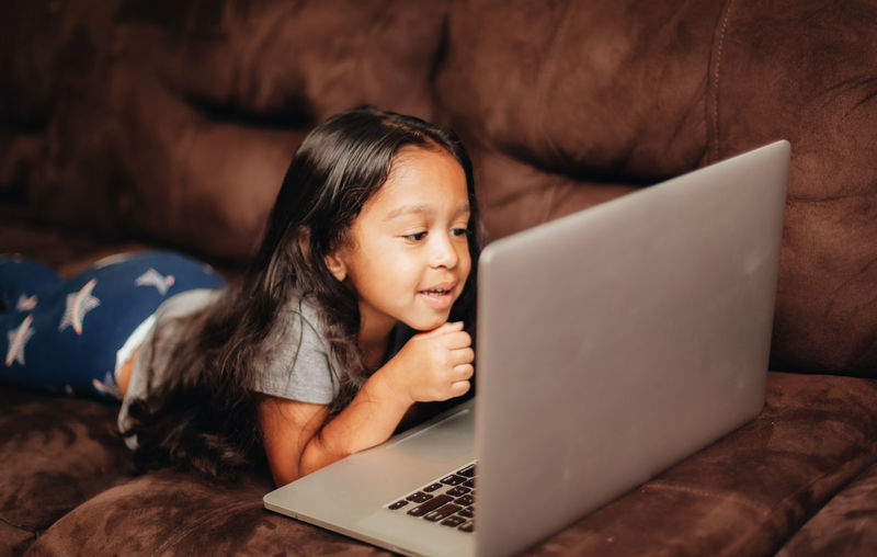 Cute girl using laptop while lying on sofa at home