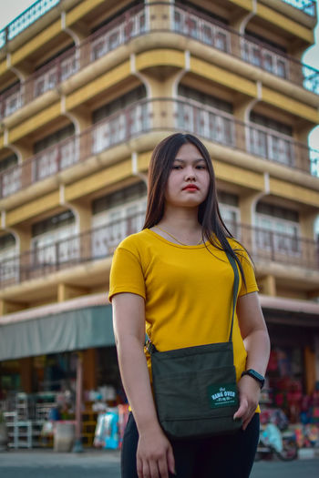 Portrait of beautiful young woman standing against yellow city