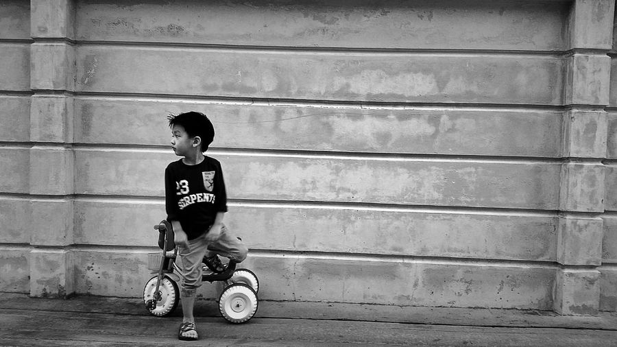 Boy Wit Tricycle Standing Against Wall On Sidewalk