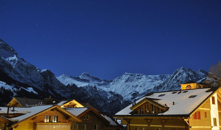 Houses and snowcapped mountains against star field