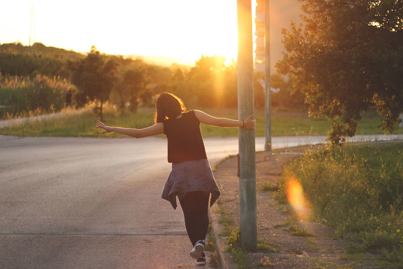 Beauty In Nature Casual Clothing Full Length Girl Grass Jacket Lens Flare Lifestyles Nature Orange Color Outdoors Outfit Running Street Streetphotography Sun Sunbeam Sunlight Sunny Sunset Tranquility Tshirt Woman Summer