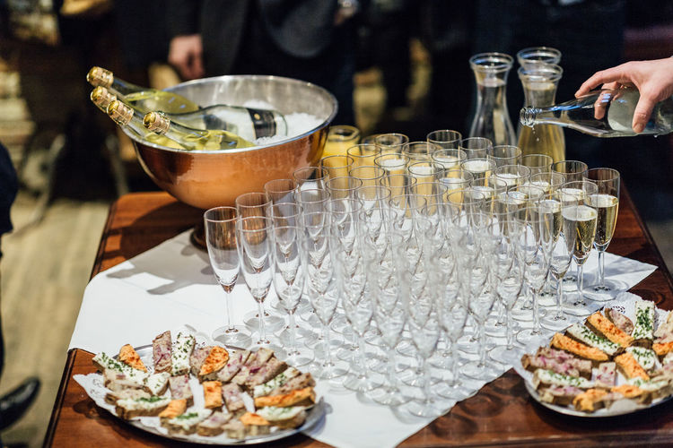 Food And Drink Food Table Freshness Drink Refreshment Incidental People Real People Indoors  Glass Alcohol One Person Restaurant Household Equipment Holding Ready-to-eat Sweet Food Container Unrecognizable Person Hand Tray Bottle Glasses Celebration Celebrating Champagne Catering Bread Reception