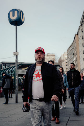Streetwise Photography Real People Lifestyles People Walking Casual Clothing Architecture Men Front View Day Young Men City Street Young Adult Standing Incidental People Focus On Foreground Built Structure Sky Streetphotography Vienna The Art Of Street Photography The Street Photographer - 2019 EyeEm Awards