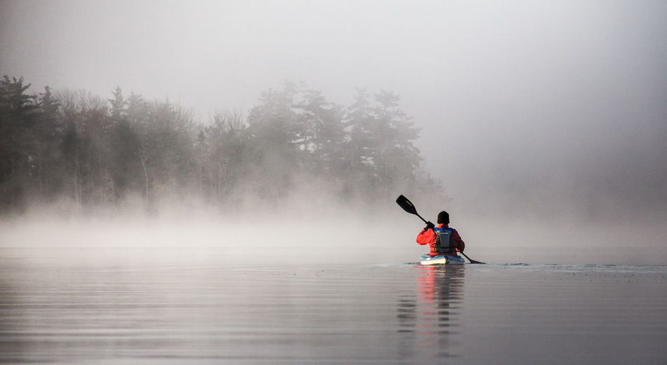 Rear View Of Man Kayaking In River During Foggy Weather