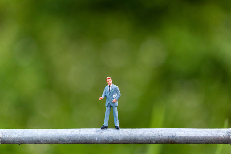 Background Business Businessman Closeup Concept Figure Figurine  Financial Green Greeting Human LINE Little Macro Male Man Mini Miniature Model Natural Nature People person Professional Small Standing Success Tiny Toy Worker World