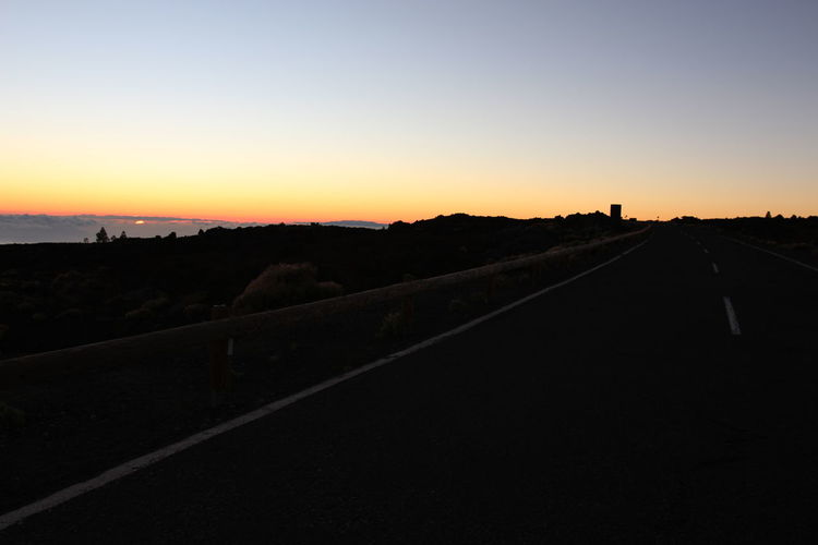 Road amidst silhouette landscape against clear sky during sunset