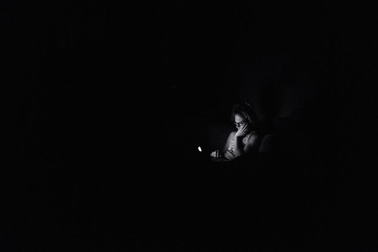 Low angle view of girl sitting against black background