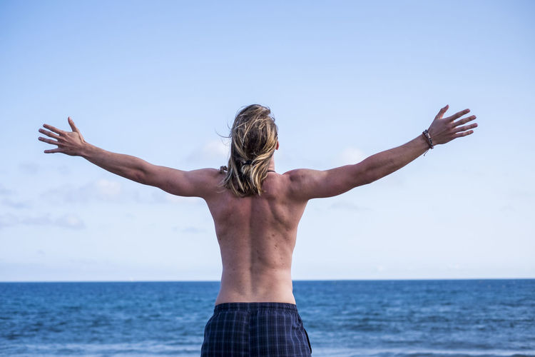 Rear view of shirtless man standing with arms outstretched against sky