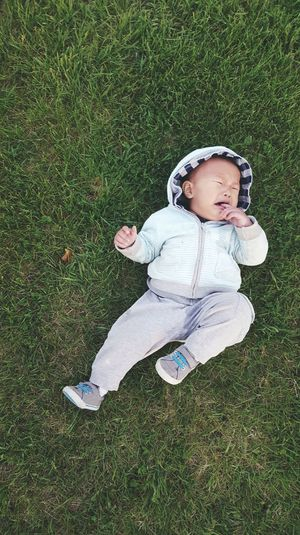Full length of baby boy crying while lying on grass