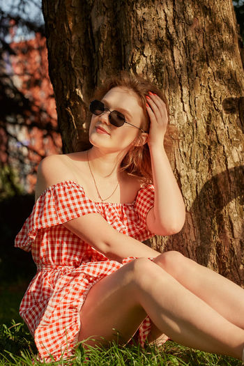 Beautiful young woman sitting on tree trunk against plants
