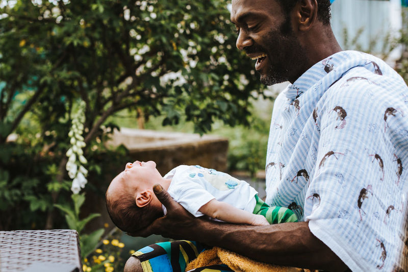 joyful and proud black man holding his baby boy Baby Emotions Family Fatherhood Moments Love Proud Relationship Black Caring Child Emotional Father Father & Son Fatherhood  Holding Joy Lifestyles Newborn Outdoors Pride Protection Safety Smile Son Summer 50 Ways Of Seeing: Gratitude