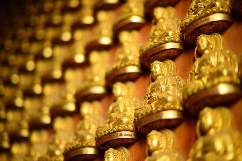 Full frame shot of golden buddha statues on wall