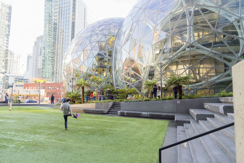 Amazon Spheres located in downtown Seattle at the world headquarters employees enjoying frisbee game on lawn. Architecture Campus Condominiums Economy Employee Giant Growing Jeff Bezos Modern Shopping Terrariums Adult Adults Only Amazon Architecture Building Exterior Built Structure City City Life Day Design Editorial  Expansion Grass Green Houses Internet Lifestyles Men Modern Only Men Outdoors People Sky Skyscraper Spheres Sport Sportsman Technology Tree World Headquarters