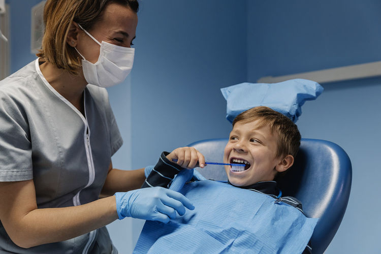 Boy learning how to brush his teeth at the dental concept. Dental Dentist Dentistry Diagnosis Healthcare Hospital Blue Boy Brush Child Clinic Clinical Equipment Expertise Gloves Kid Mask Odontology Orthodontist  Professional Team Teeth Tooth Toothbrush Treatment