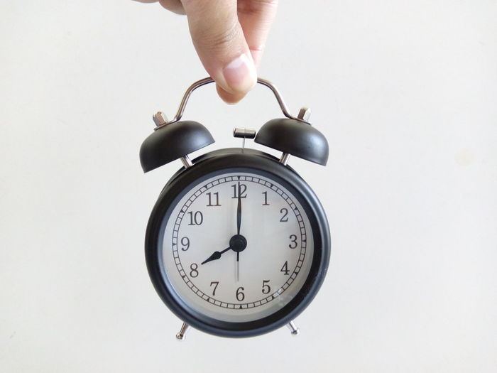 Cropped hand of person holding alarm clock against white background