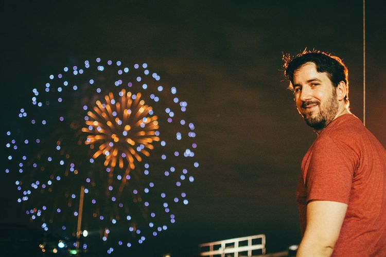 Portrait of young man standing against sky with fireworks at night