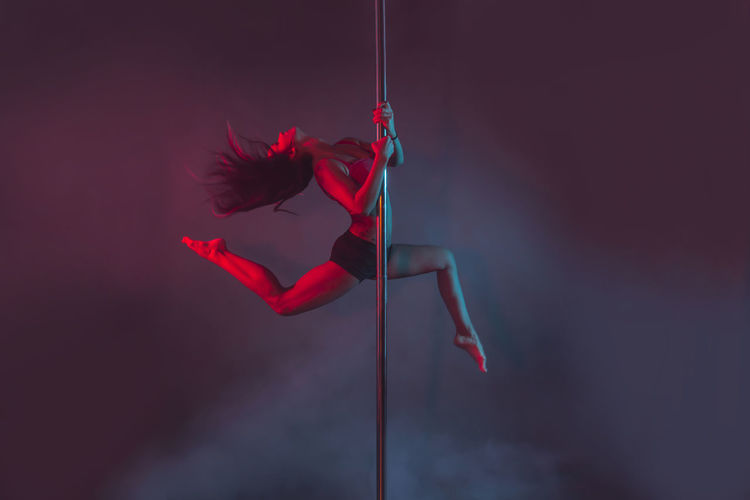 Young Pole Dancer Performing Against Colored Background