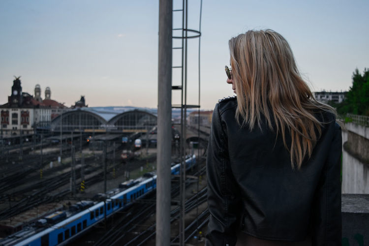 Young woman with blond hair standing by shunting yard against sky during sunset