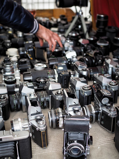 Cropped image of hand touching cameras for sale in flea market