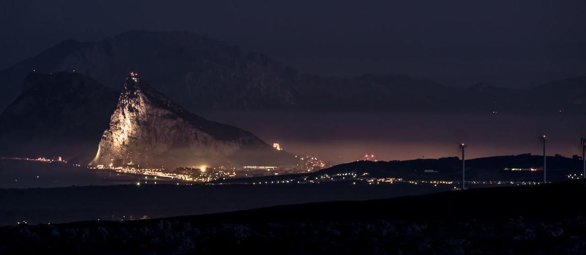 Illuminated mountain by sea against sky at night