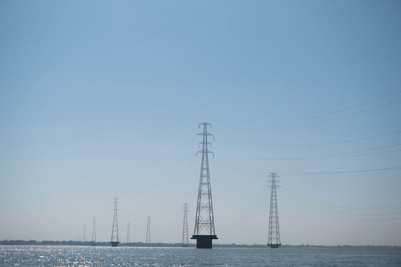 Electricity Pylons On Sea Against Clear Sky