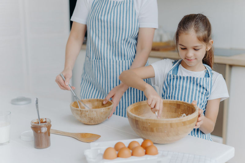 Midsection of woman making food while standing by girl