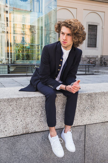 Full length of man looking away sitting in city