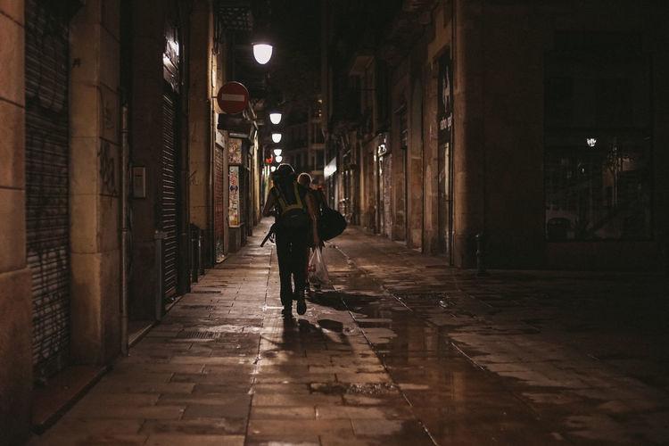 Man walking on wet street at night