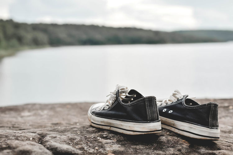 Close-up of shoes on rock against lake