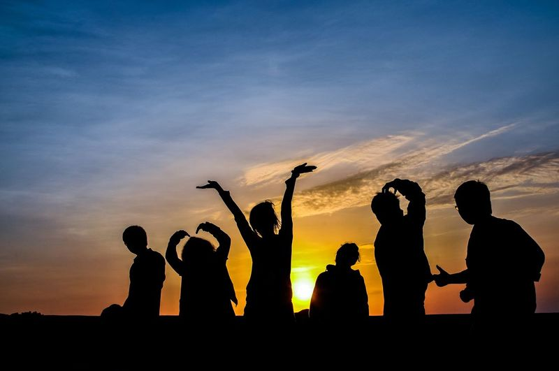 Silhouette friends standing against sky during sunset