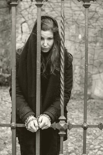 Sad woman tied with chain on gate against wall