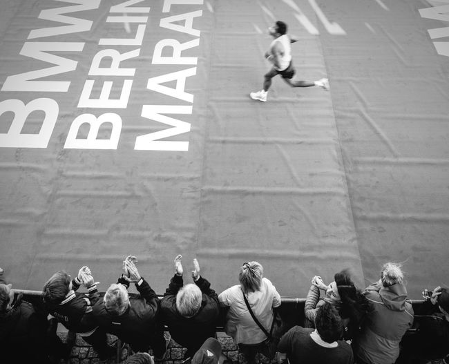 High Angle View Of Spectators Cheering For Man Running In Marathon