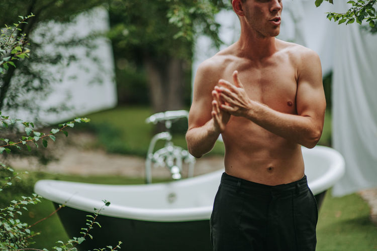 Midsection of shirtless man standing against blurred background