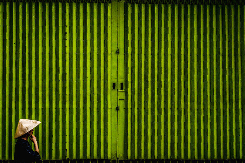 Man standing by green gate