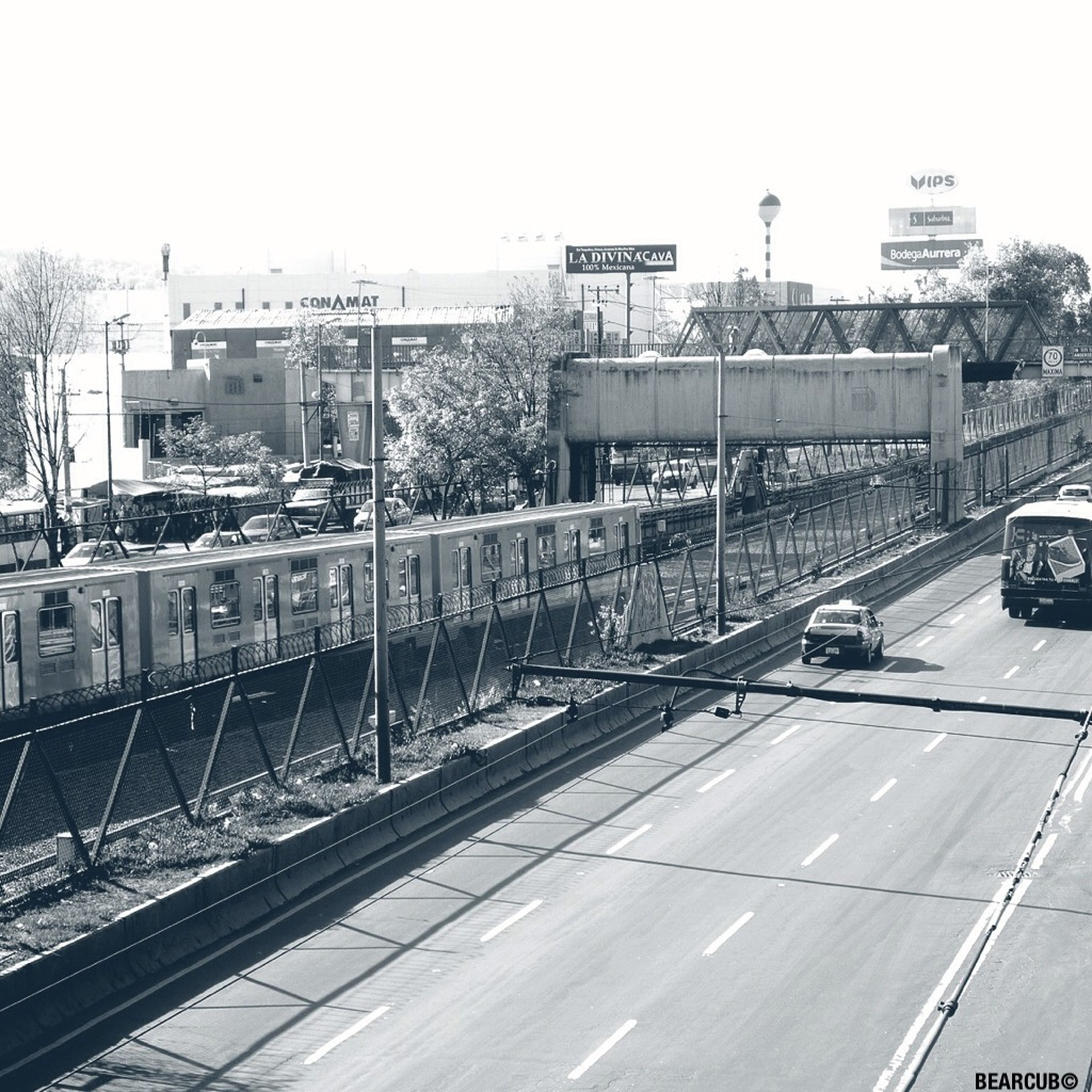 transportation, railroad track, city, high angle view, architecture, building exterior, built structure, mode of transport, public transportation, rail transportation, clear sky, car, land vehicle, railroad station platform, road, railroad station, road marking, train - vehicle, city life, street