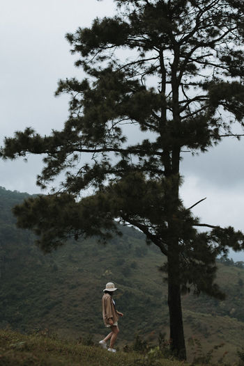 Full length of woman walking on hill against tree