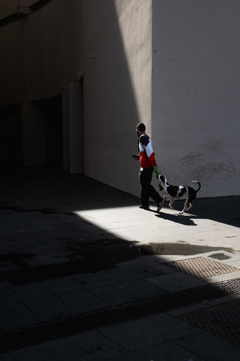 Side view of man walking on footpath against building